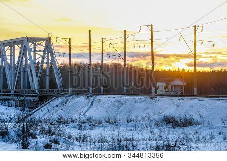 railway bridge over the Kem river in Karelia, Russia, at sunset in winter