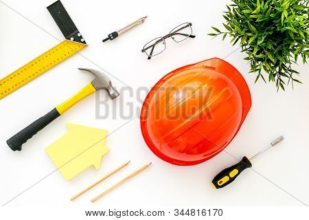 Construction Concept. Helmet, Tools On Work Desk, House Cutout On White Wooden Background Top-down P