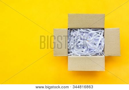 Top View Reuse Shredded Paper Documents In Brown Paper Cardboard Isolated On Yellow Background With