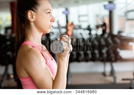 Slim Beautiful Woman Wearing Pink And Black Sportswear Doing Exercise Using Dumbbells In A Gym. Spor