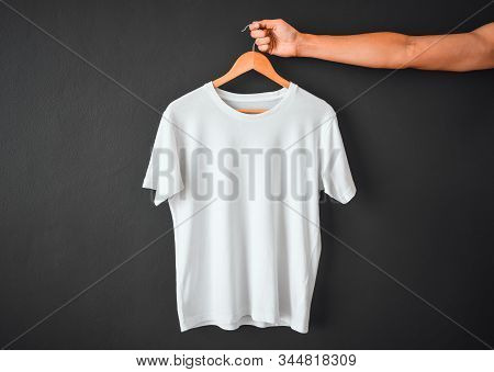 Close Up Of Hand Holding White Color T-shirt Hanging On Wooden Cloth Hanger Over Black Color Backgro