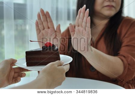 Fat Woman Pushes The Plate Onto A Chocolate Cake. Intention To Lose Weight For Good Health And Good