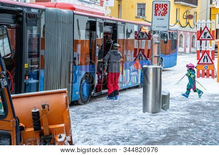 St. Mortiz, Switzerland - 22 December 2019 - Young Boy And His Dad Catch A Public Bus To Go Skiing A