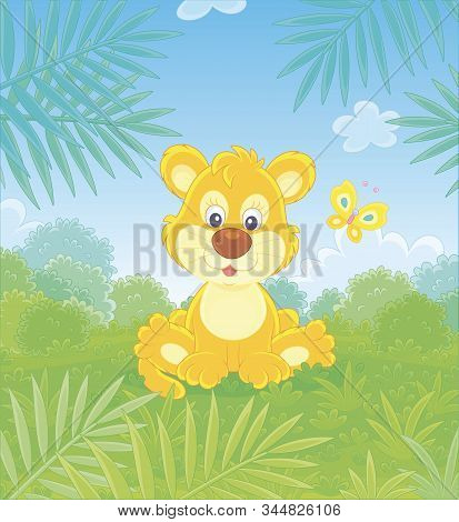 Little Lion Playing With A Small Colorful Butterfly Against The Background Of Palm Branches And Bush