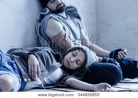 Homeless Young Man And Woman Are Lying On Cardboard On Floor In Abandoned House. Guy And Girl Addict
