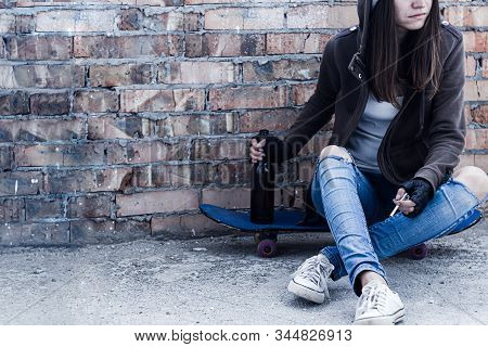 Young Woman In Hood Is Sitting On Skateboard And Holding Smoldering Cigarette And Bottle Of Beer. Ho