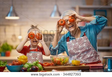 Healthy food at home. Happy family in the kitchen. Grandma and child are preparing the vegetables .
