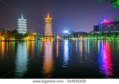 Guilin, Guangxi Province, China - Nov 5, 2019 : Sun And Moon Pagodas Illuminated At Night Reflecting