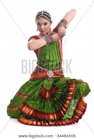 Bollywood dancer in green and orange folded dress posing as cobra