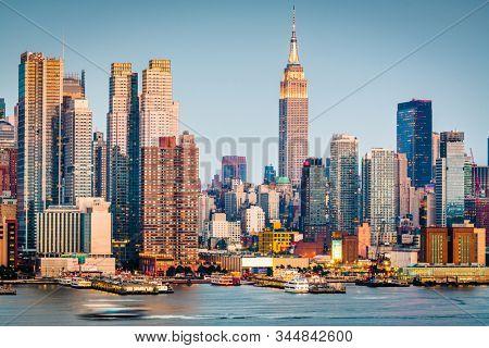 New York, New York, USA downtown city skyline on the Hudson River at dusk.