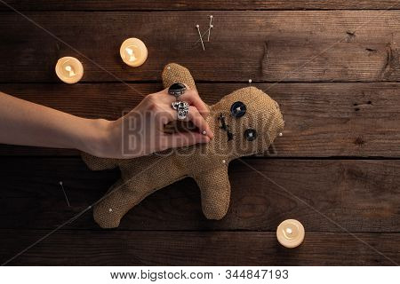 Voodoo Doll On A Wooden Background With Dramatic Lighting And Candles. The Concept Of Witchcraft And