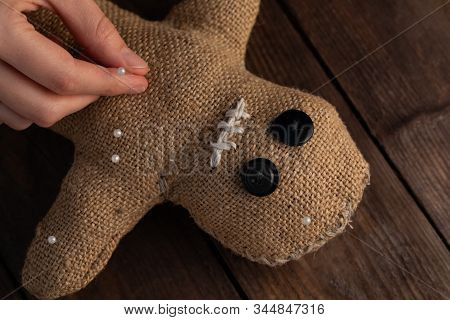 Voodoo Doll On A Wooden Background With Dramatic Lighting. The Concept Of Witchcraft And Black Art.