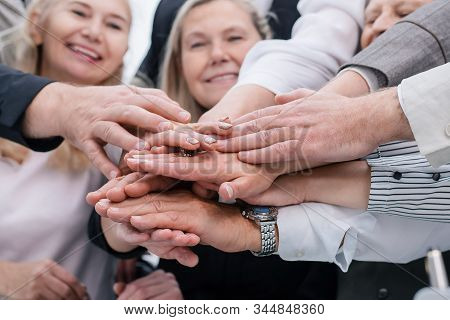 Close Up. A Group Of Diverse Employees Joining Their Palms Together.