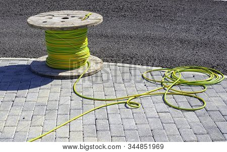 Wire Electric Cable With Wooden Coil Of Electric Cable Waiting To Be Slipped Into The Conduit
