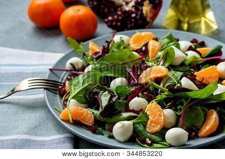 Fresh  Mixed Green Salad With Mandarins, Pomegranate Seeds And Mozzarella.