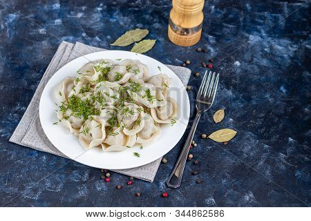 Boiled Dumplings On A White Plate. In The Background Is A Wooden Hodgepodge, Greens, Red Peppers And