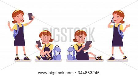 School Girl With Gadgets, Phone, Tablet. Cute Small Lady In A Pretty Pinafore Dress With Rucksack, A