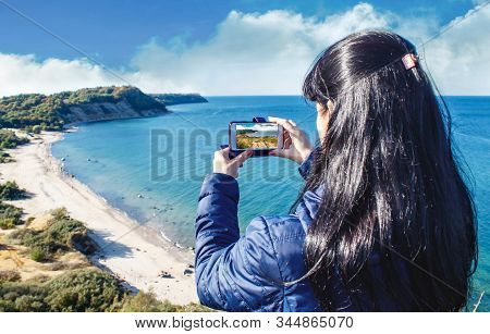 Brunette Woman In Blue Jacket Photographing Seascape By Smartphone On Sunny Autumn Day