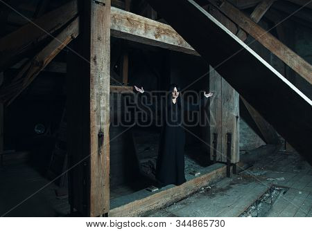 Gothic Brunette Woman Standing In Attic Of Dark Gloomy Abandoned House