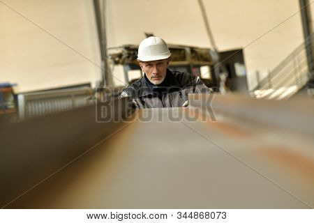 Steelworker with security helmet working in plant