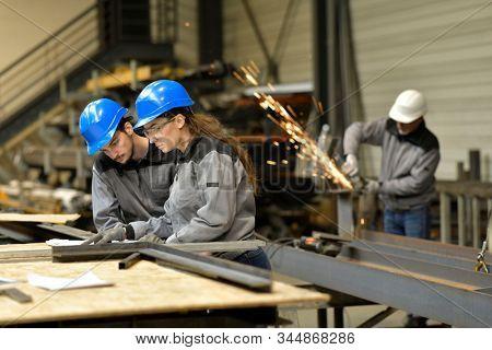 Apprentice working in steelwork factory