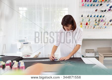 Young Female Dressmaker Making A Pattern On A Piece Of Dark Cloth. Portrait Of Fashion Designer Work