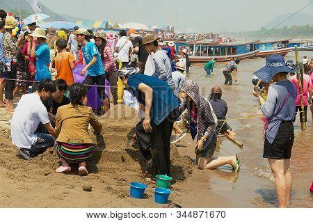 Luang Prabang, Laos - April 13, 2012: People Build Sand Pagoda At The Mekong River Bank During Lao N