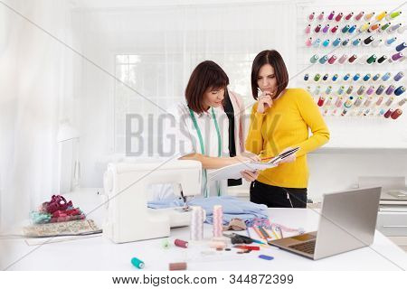 Two Young Female Dressmakers Working In Sewing Studio. Seamstress Select Color Of Threads Suitable F