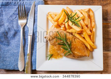 Chicken Breast Marinated And Cooked With Rosmery Sauce And French Fries