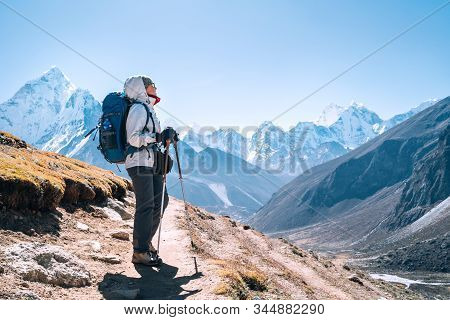 Young Hiker Backpacker Female Taking A Walking With Trekking Poles During High Altitude Everest Base