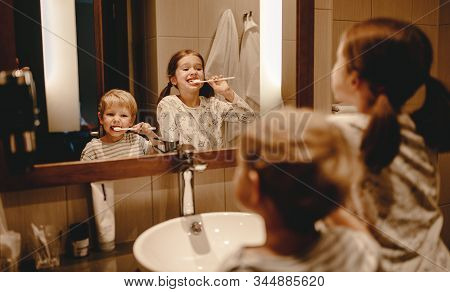 Happy Funny Kids Boy And Girl Brushing Their Teeth At Home In The Bathroom