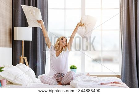 Happy Young Woman Laughing And Jumping On The Bed In The Morning At Home