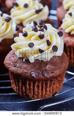 Close-up Of Chocolate Cupcake Topped With Vanilla Buttercream Swirl Icing On A Metal Cake Rack On A