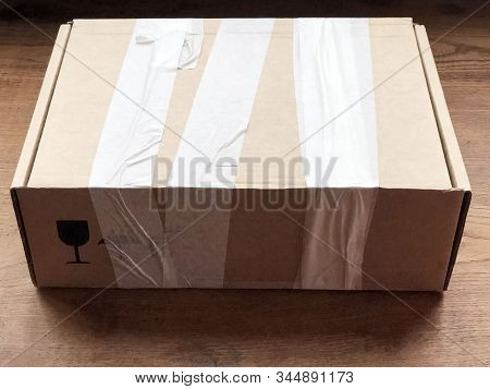 Closed Cardboard Box On Wooden Background Covered With Duct Tape And Glass Sign. Shipping Equipment
