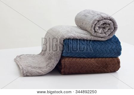 Stack Of Folded Soft Blankets On The White Table