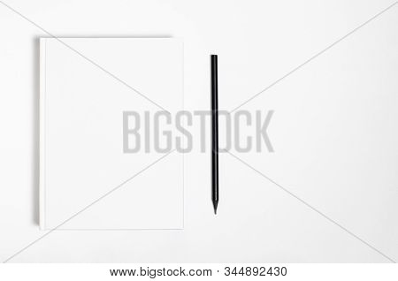 Mockup Of Closed Blank Square Book And Black Pencil At White Textured Paper Background