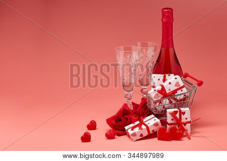 Shopping trolley, gift boxes, red roses and hearts, champagne and flutes on pink background with copy space. Valentine's Day. Festive background with decorative hearts.Valentine's Day. Wedding day.