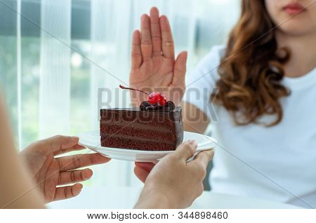 Healthy Women Push The Plate Into Chocolate Cake. Refusing To Eat Foods That Contain Trans Fats And