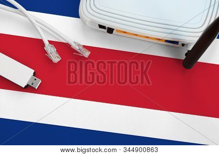 Costa Rica Flag Depicted On Table With Internet Rj45 Cable, Wireless Usb Wifi Adapter And Router. In