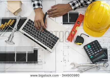 Engineers Work With Laptops And Blueprints. Calculate And Check The Construction Project.