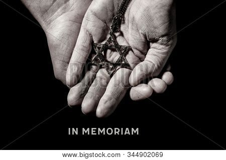 an old and rusty pendant in the shape of the star of david on the hands of a man and the text in memoriam, a latin phrase equivalent to in memory, as a memory of the dead jewish people