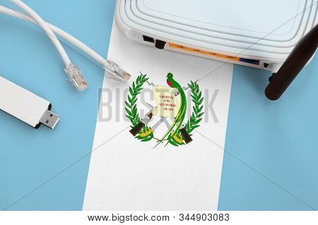 Guatemala Flag Depicted On Table With Internet Rj45 Cable, Wireless Usb Wifi Adapter And Router. Int
