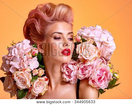 Beautiful white girl with flowers. Stunning blonde girl with big bouquet flowers of roses. Closeup face of young beautiful woman with a healthy clean skin. Pretty woman with bright makeup