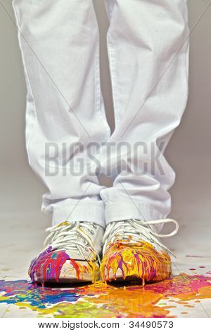 Girl in white sneakers stained by paint