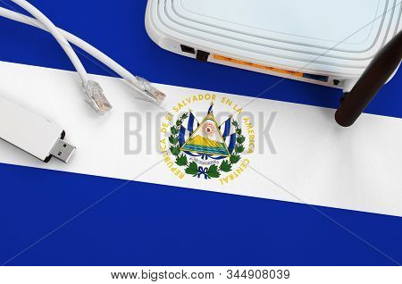 El Salvador Flag Depicted On Table With Internet Rj45 Cable, Wireless Usb Wifi Adapter And Router. I