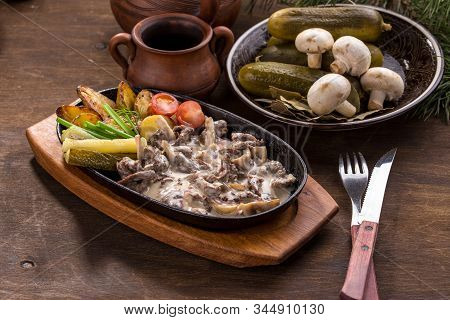 Beef Stroganoff With Baked Potatoes, Mushroom And Pickles On Wooden Table
