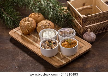 Various Dip Sauces And Appetizer And Bread Bun On Wooden Table