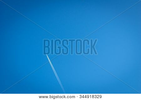 Airplane Flying Through Clear Blue Sky With Vapour Trails