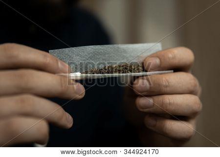 Man Rolling A Marijuana Joint. Man Preparing And Rolling Marijuana Cannabis Joint. Close Up Of Addic