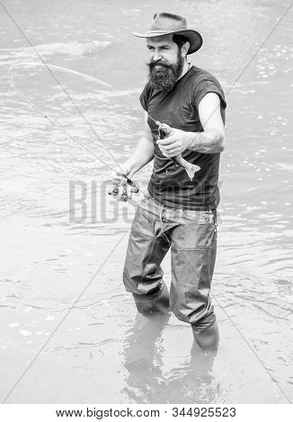 Brutal Man Wear Rubber Boots Stand In River Water. Fisher Weekend Activity. Fisher With Fishing Equi